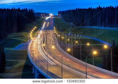 Night lighting of the highway bridge in the forest.