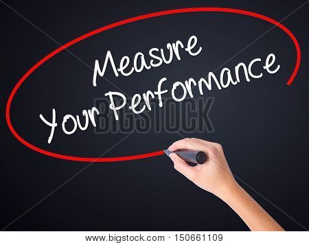 Woman Hand Writing Measure Your Performance With A Marker Over Transparent Board