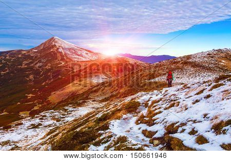 Walking Hiker in Red Jacket with Backpack on Snow Slope distant Mountain Ridges stacked on Background