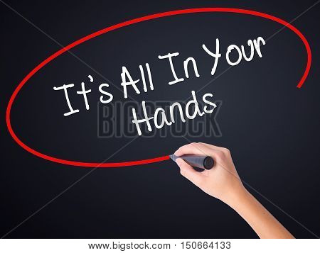 Woman Hand Writing It's All In Your Hands  With A Marker Over Transparent Board .