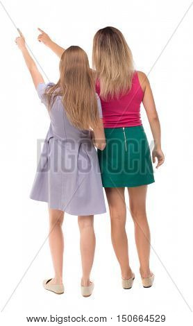 Back view of two pointing young girl. Rear view people collection.  backside view of person. beautiful woman friends  showing gesture. Rear view. Isolated over white background. Two girls show his