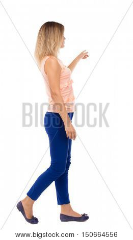 back view of pointing walking  woman. going girl pointing.  backside view of person.  Rear view people collection. Isolated over white background.The blonde in a pink t-shirt goes to the side pointing