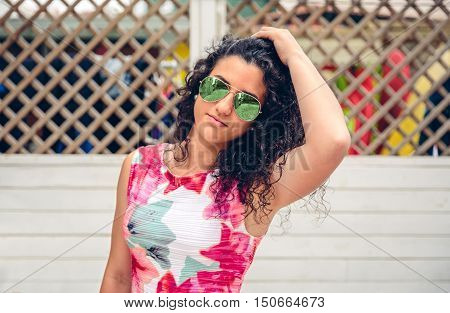Portrait of curly young woman with sunglasses looking at camera over white garden fence background