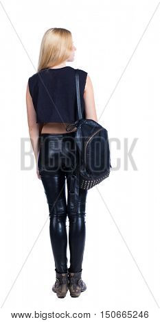 back view of standing young beautiful  woman.  girl  watching. Rear view people collection.  backside view of person.  Blonde in leather pants standing with backpack standing and looking sideways.