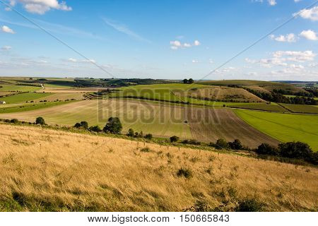 Farmer sowing seeds on field in Wiltshire, England. Tractor planting crops in field in front of Middle Hill in the Imber Range in the British autumn