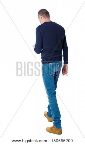 back view of a man walking with a mobile phone. back view of man in motion.  backside view of person.  Rear view people collection. Isolated over white background. The guy in the black sweater is