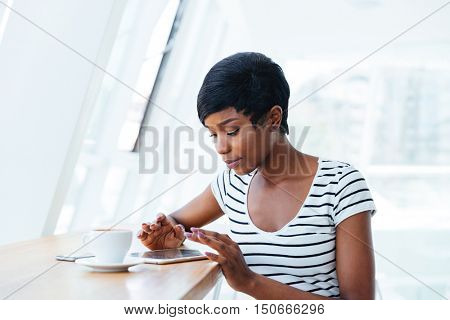 Pretty african businesswoman using tablet amd having coffee break in office