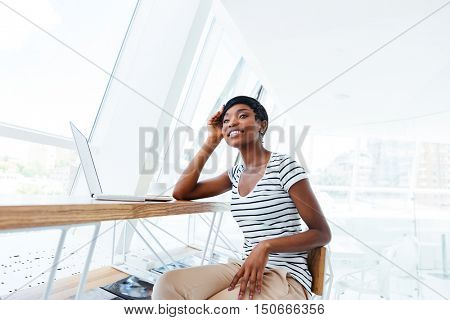 Cheerful attractive african businesswoman sitting and working with laptop in office