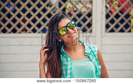 Portrait of young woman with sunglasses and long hair looking at camera over white garden fence background