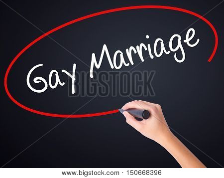 Woman Hand Writing Gay Marriage With A Marker Over Transparent Board .