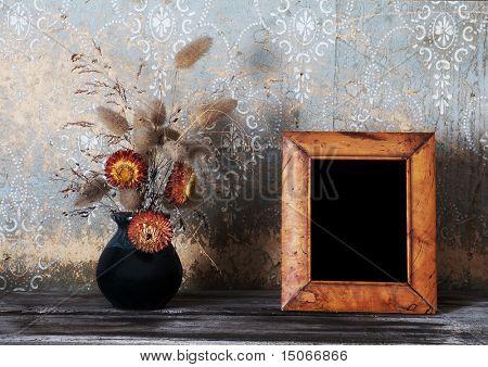 vintage photo-frame and ikebana on old table