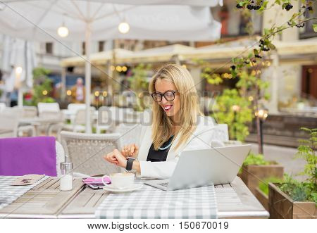 Woman sitting in cafe and using digital touch screen watch