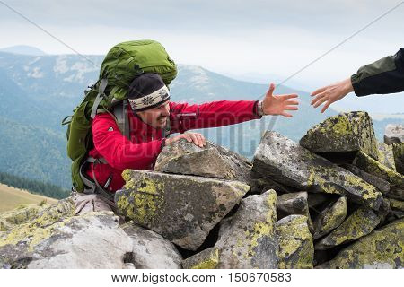 Friendly Hand on the High Mountain Hike. Men Helping Other Hiker by Giving Him Hand. Hiking Theme. Mountain instructor handed someone a helping hand to the top of the mountain. Concept teamwork.