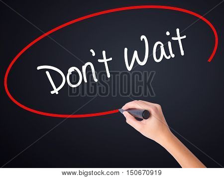 Woman Hand Writing Don't Wait  With A Marker Over Transparent Board