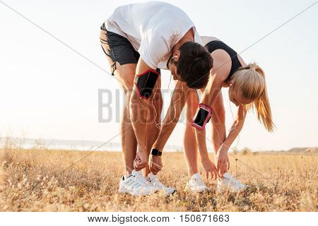 Young couple tying their shoes and getting ready for running and working out together outdoors