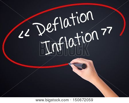 Woman Hand Writing Deflation - Inflation With A Marker Over Transparent Board .