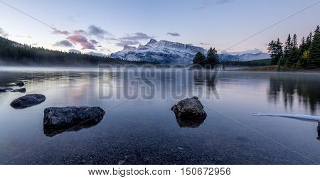 Rundle Mountain reflecting in Two Jack Lake in Banff National Park at sunrise.