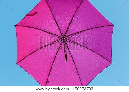 Underside of a pink umbrella with rain drops.