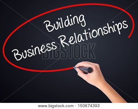 Woman Hand Writing  Building Business Relationships  With A Marker Over Transparent Board