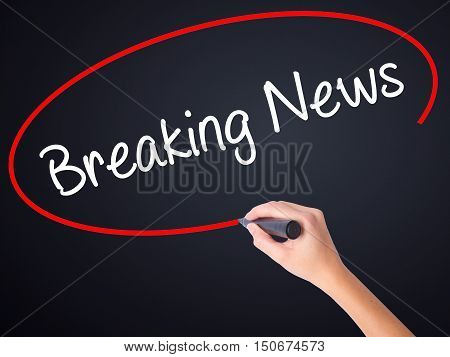 Woman Hand Writing Breaking News With A Marker Over Transparent Board