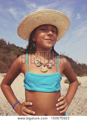 Little Girl In A Bathing Suit On The Beach Wears A Necklace Of Shells