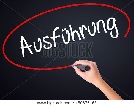 Woman Hand Writing Ausfuhrung (execution In German) With A Marker Over Transparent Board