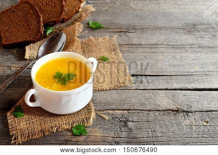 Tasty pumpkin soup with potatoes and rice. Pumpkin soup in a bowl, spoon, brown bread slices on old wooden background with empty place for text