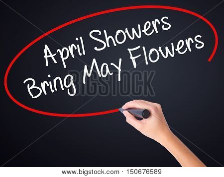 Woman Hand Writing April Showers Bring May Flowers With A Marker Over Transparent Board