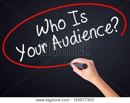 Woman Hand Writing Who Is Your Audience? With A Marker Over Transparent Board