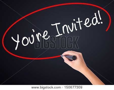 Woman Hand Writing You're Invited! With A Marker Over Transparent Board