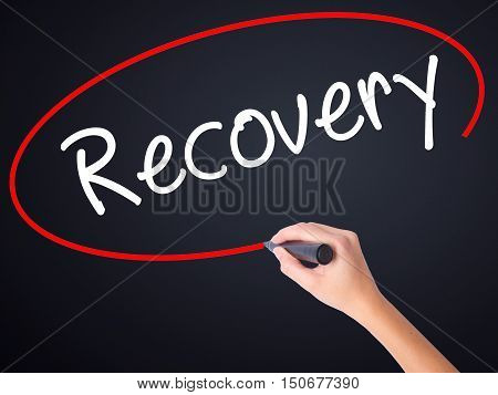 Woman Hand Writing  Recovery  With A Marker Over Transparent Board