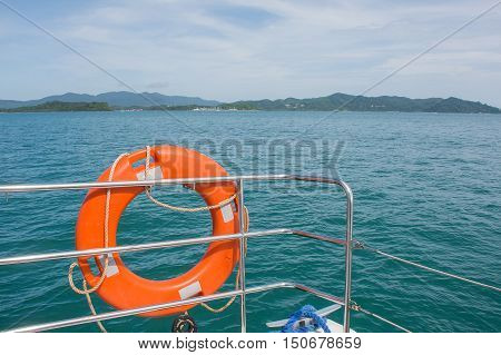 Orange life preserver (or Life Buoy)on luxury sailing yacht with beautiful blue sky cloud and Andaman sea background in sunny dayPhuketThailand