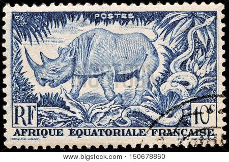 LUGA RUSSIA - APRIL 12 2016: A stamp printed by FRENCH EQUATORIAL AFRICA shows Black Rhinoceros and African Rock Python circa 1947.
