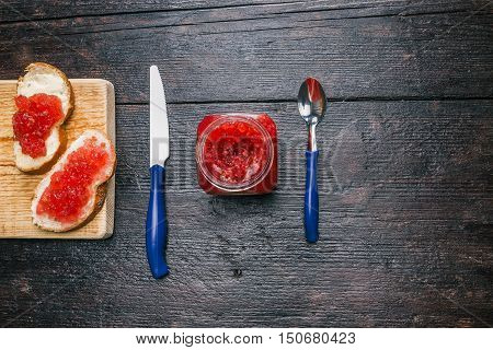 Breakfast with raspberry marmalade on the dark wood surface. Flat lay