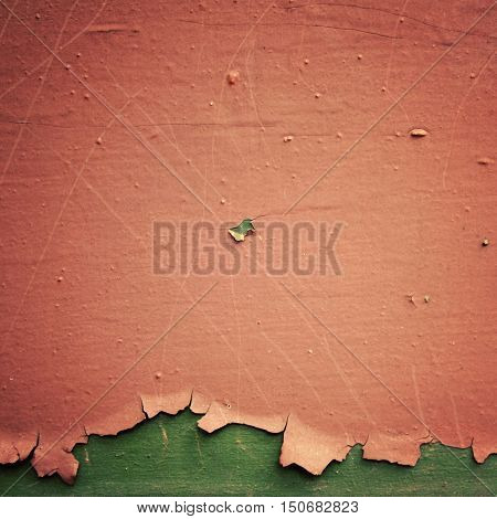 Pink paint on the green surface. Dry peeling paint on the wall. Text frame for text. Close up photo. Aged image. Abandoned place. Grunge background.
