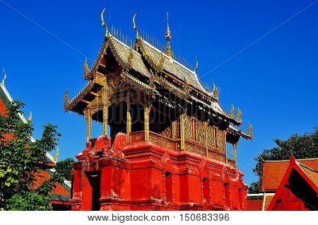 Lamphun Thailand - December 28 2012: Repository Library built on a red sandstone base with gilded roof wooden dragons and chofah ornaments at Wat Phra That Haripunchai Maha Viham *