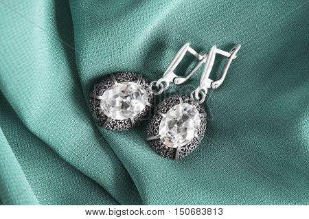 Diamond earrings on cyan silk as a background