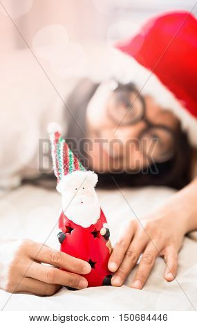 asian woman holding toy of Santa in hand lay down on white bed double exposure with bokeh light selective focus