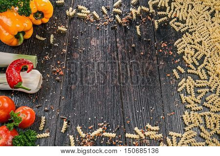 Uncooked fusilli pasta with fresh vegetable on the dark wooden table
