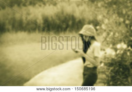 de-focused young Asian woman in garden using a mobile telephone vignette and sepia tone
