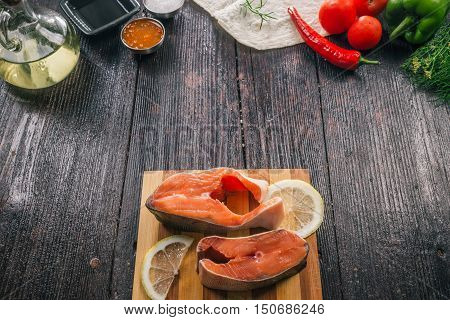 Fresh uncooked salmon steaks on the wooden table with condiments and vegetables