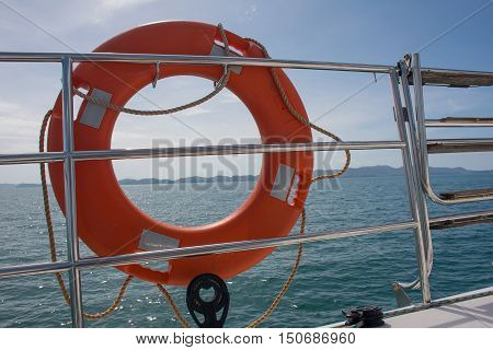 Low key image of Orange life preserver (or Life Buoy)on luxury sailing yacht with beautiful blue sky cloud and Andaman sea background in sunny dayPhuketThailand