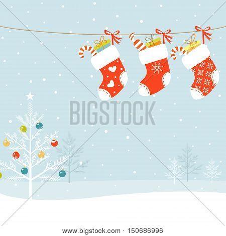 Christmas socks and Christmas tree on snowed background.