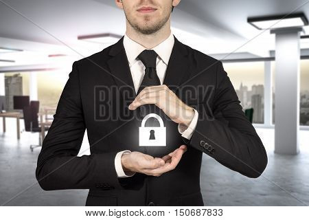 businessman in modern office protect lock symbol with hands