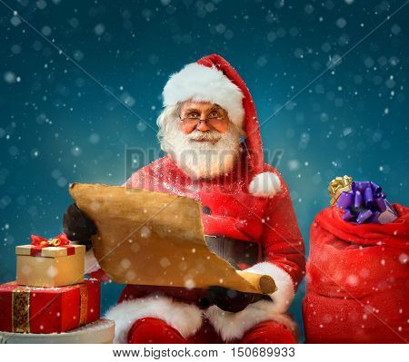 Santa Claus holding vintage paper and reads long list of gifts for children. Merry Christmas & New Year's Eve concept.