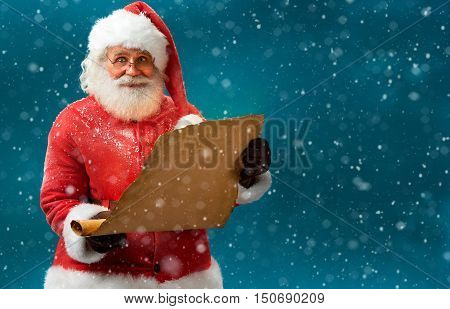 Happy Santa Claus holding vintage paper on blue background. Merry Christmas & New Year's Eve concept.