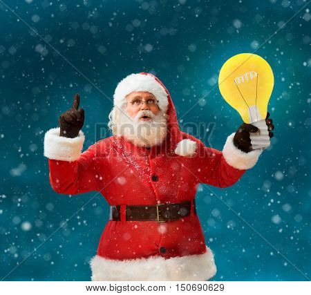 Faddish Santa Claus with open mouth and finger pointing up showing light bulb banner. Santa Claus on blue background having a good idea. Happy New Year!