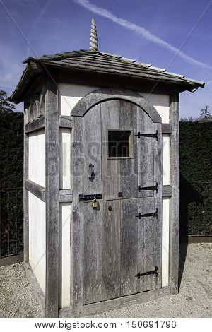 A traditional wooden sentry box with stable door and spiral filial on the tiled roof.