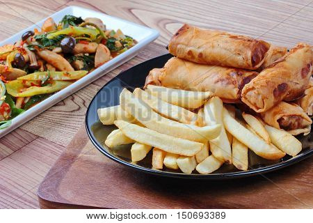 Deep fried spring roll and French fries served are food for Chinese Vegetable festival as