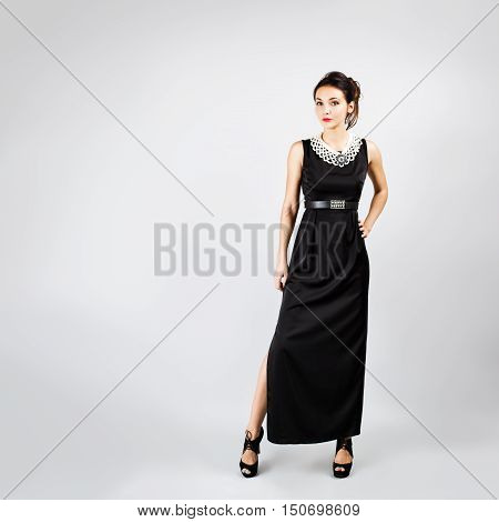 Full Length Portrait of a Brunette Woman in Black Evening Dress on Gray Background. Girl in Long Gown with Necklace and High Heels. Toned Photo with Copy Space.